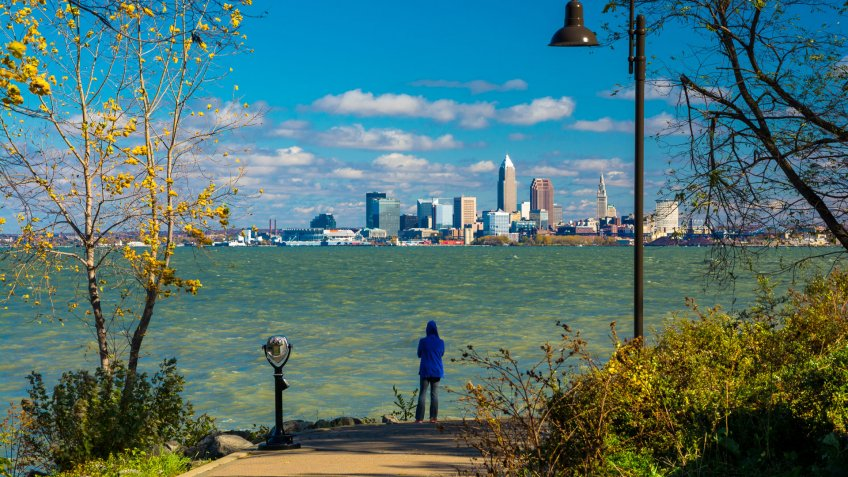 """A woman wearing a hood looks at the Cleveland Skyline from a park just beside Lake Erie""""n."""