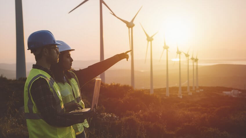 Young electrical engineer woman and business man standing in front of wind turbines checking and working about technical problems and writes the results of measurements with laptop pc in wind power plant electric energy station.