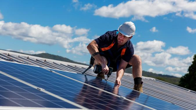 Solar panel installer with drill installing solar panels on roof on a sunny day.
