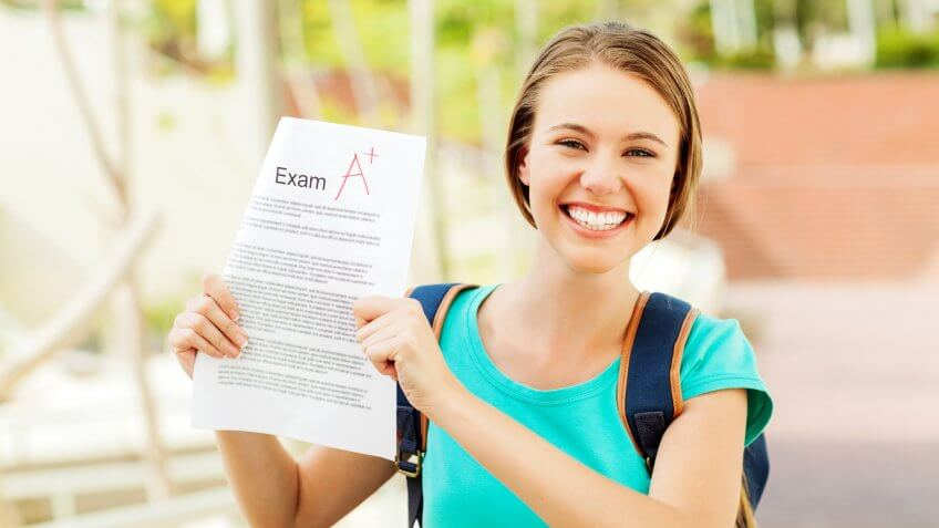 Portrait of happy teenage girl showing test result with A+ grade on university campus.