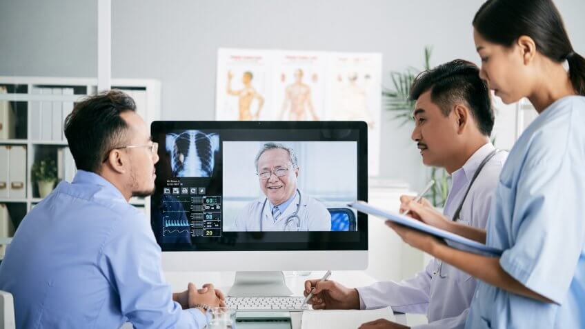 Asian medical interns consullting with doctor online.
