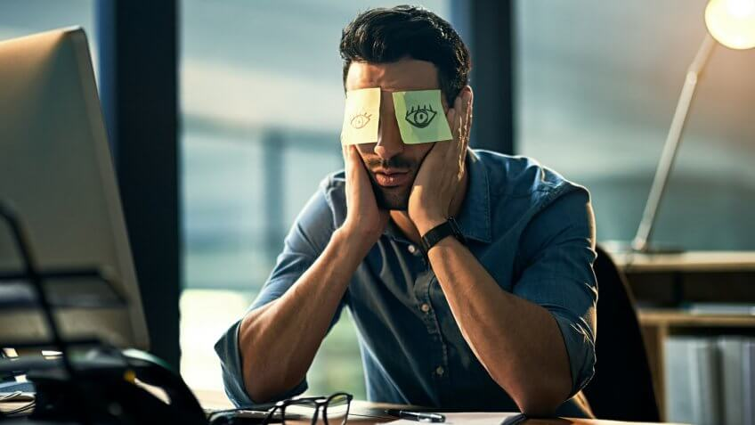Shot of a tired young businessman working late in an office with adhesive notes covering his eyes.