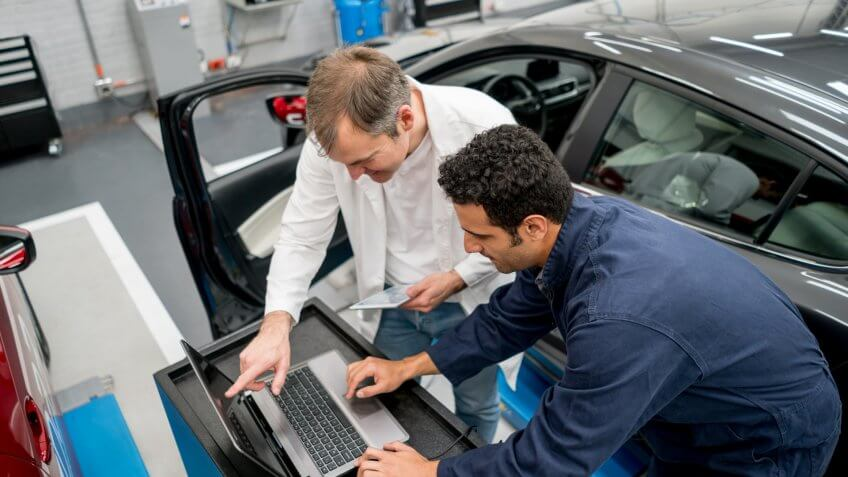 Team of mechanics working together at an auto repair shop using a computer to fix a car.