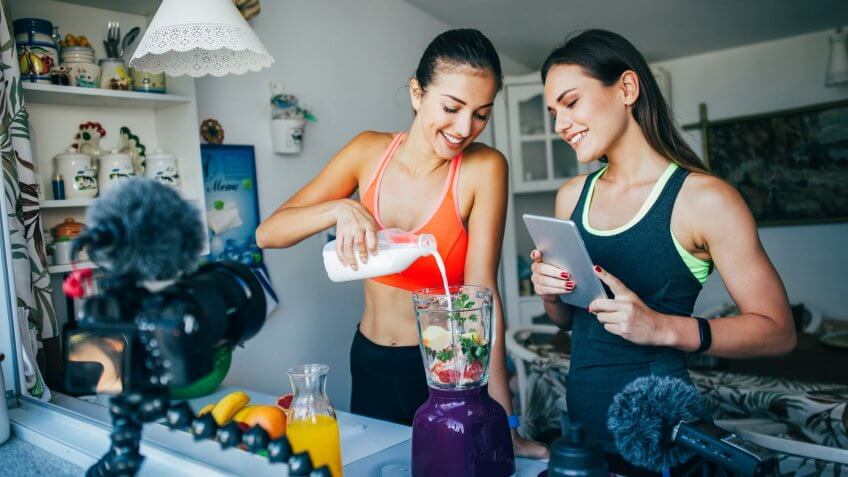 Two women making a smoothie in a vlog.