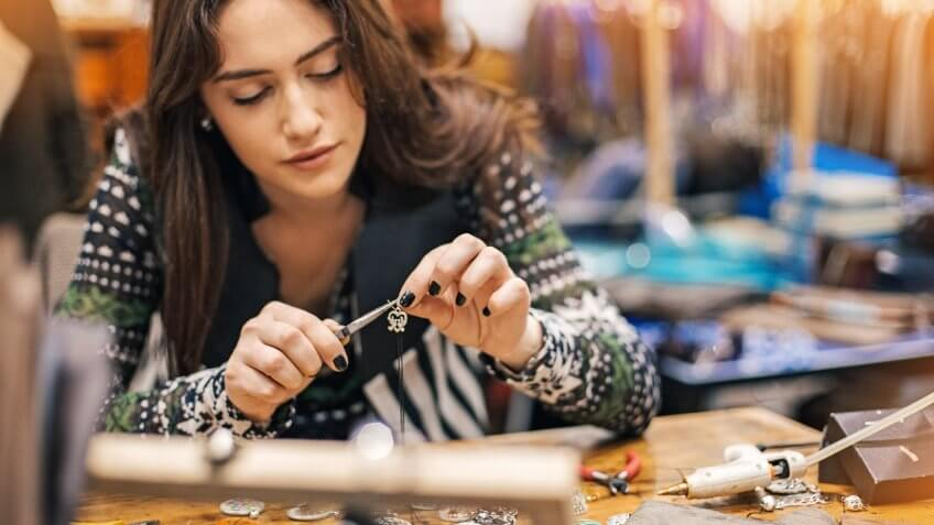 Young woman creating handmade jewelry in her studio.