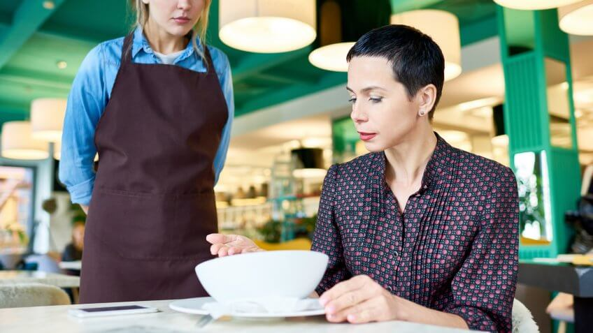 Portrait of elegant woman  complaining about food quality and taste to young waitress in cafe.
