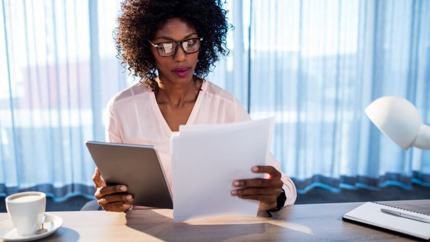 Businesswoman holding a tablet and reading a document in office.