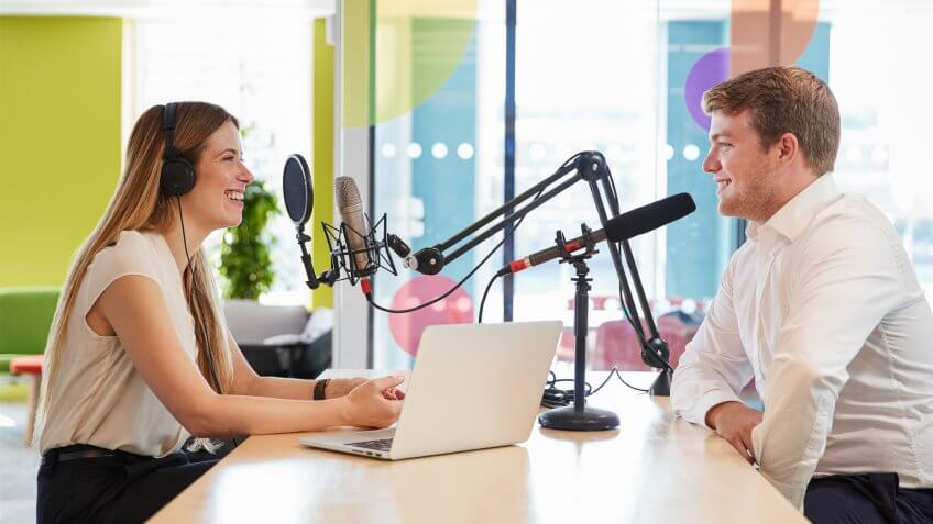 Young woman interviewing a guest in a studio for a podcast.