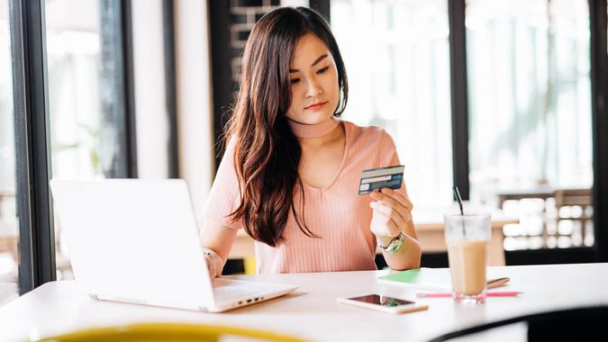 woman looking at her credit card