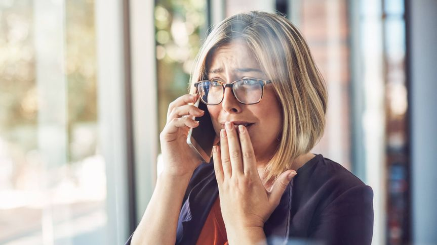 young woman looking stressed while talking on a mobile phone in a modern office.
