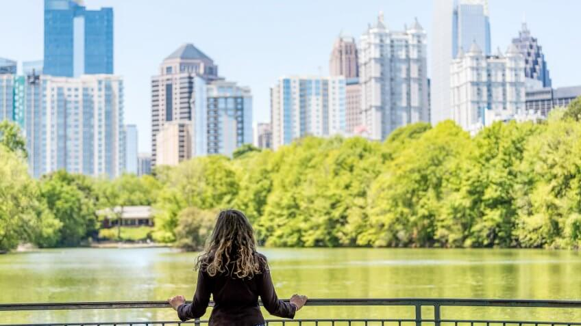 Young woman standing in Piedmont Park in Atlanta, Georgia looking at scenic water, and cityscape skyline of urban city skyscrapers downtown, Lake Clara Meer.