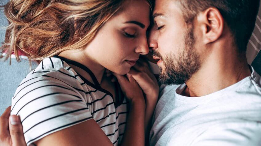Attractive Young Couple Laying In Bed In Consoling Embrace.