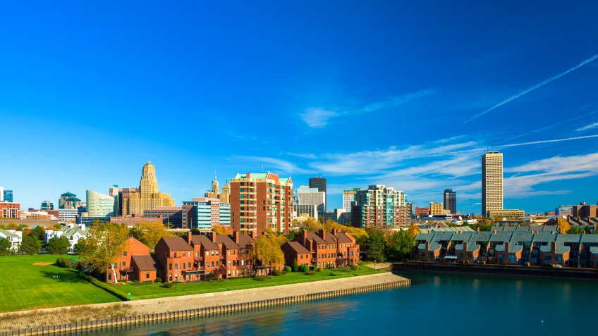 Downtown Buffalo skyline with a wterway and residential buildings in the foreground.