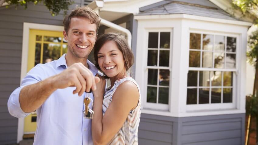 Couple With Keys Standing Outside New Home.