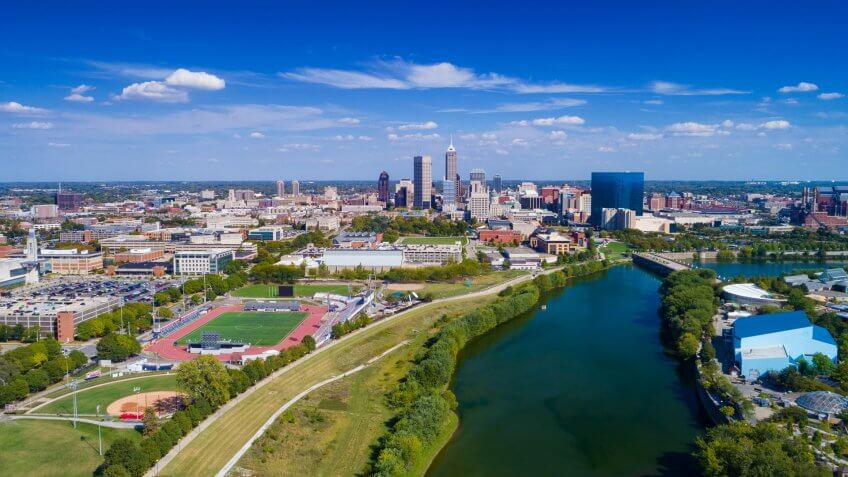 Indianapolis aerial view with Downtown Indianapolis and a blue sky with clouds in the background, and White River and Indiana University - Purdue University Indianapolis(left) and Indianapolis Zoo (right) in the foreground.