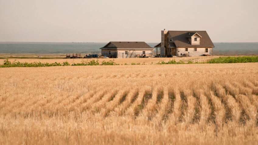 A house amidst the fields of grain in the midwest in the early evening.