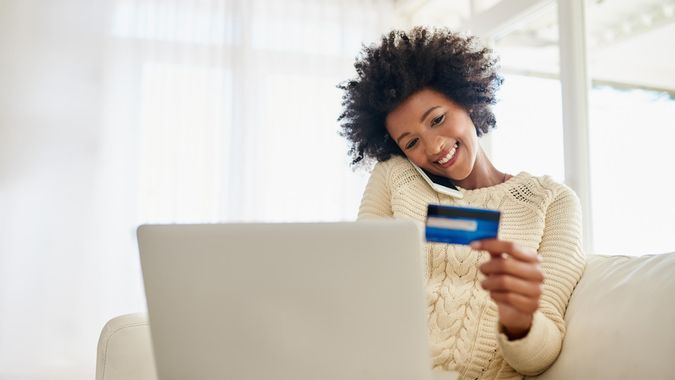 young woman on her phone holding credit card while using her laptop while sitting on the sofa at home
