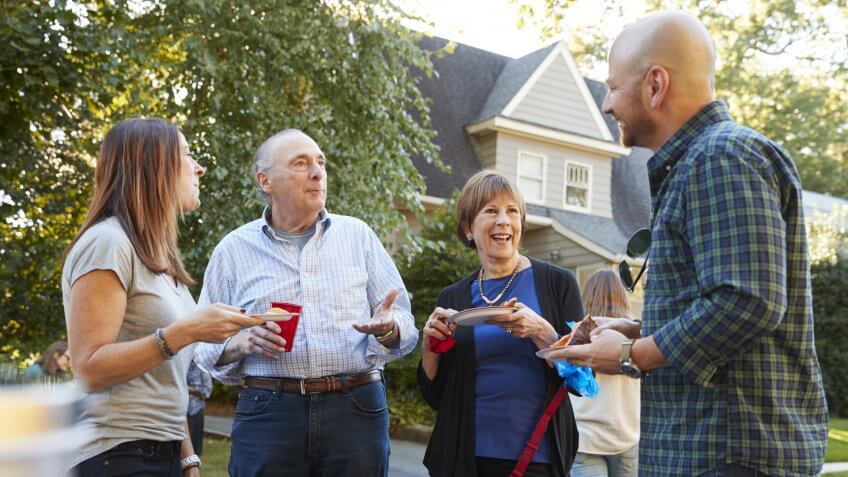 Middle aged and senior neighbours talking at a block party.