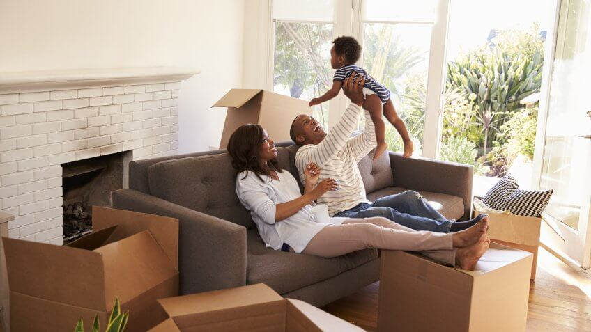 Parents Take A Break On Sofa With Son On Moving Day.