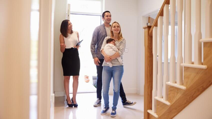 Realtor Showing Young Family Around Property For Sale.
