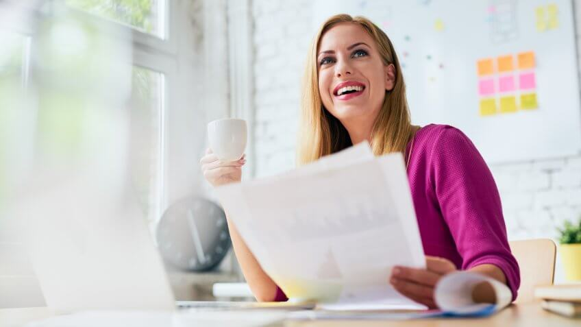 Smiling woman working at office, drinking coffee and browsing documents.