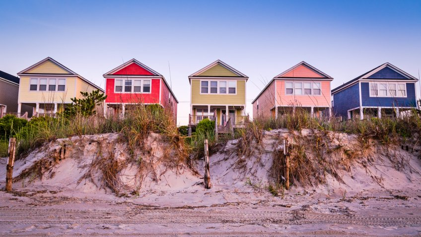 A summer scene on the beach with cottages in a line.
