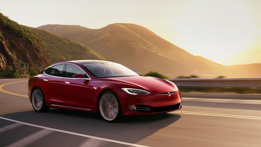 Tesla Model S Red driving at sunset