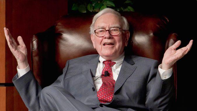 Warren Buffet makes hand gesture on chair