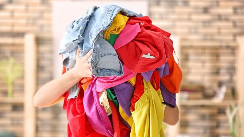 Woman holding pile of colorful clothes indoors.
