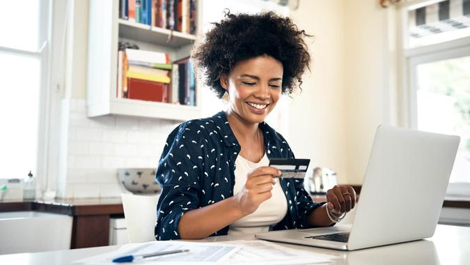woman smiling at credit card in her home