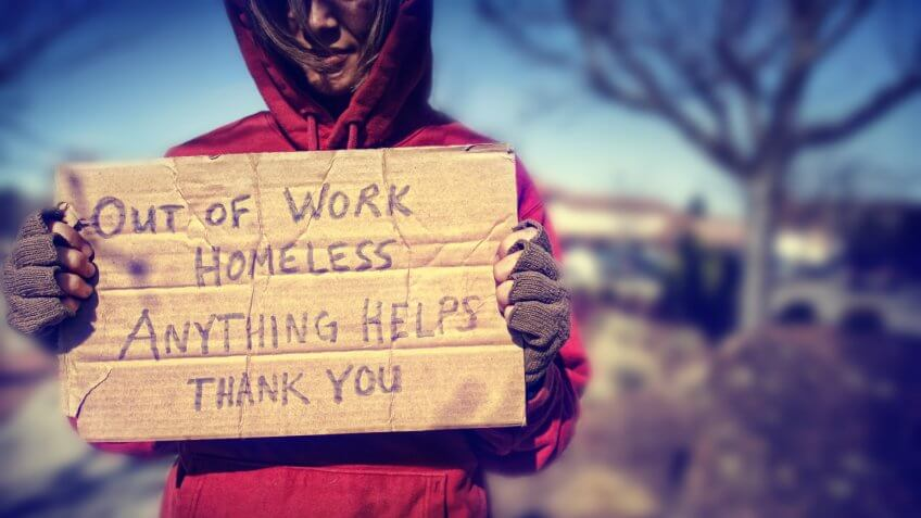 a homeless person with a sign.