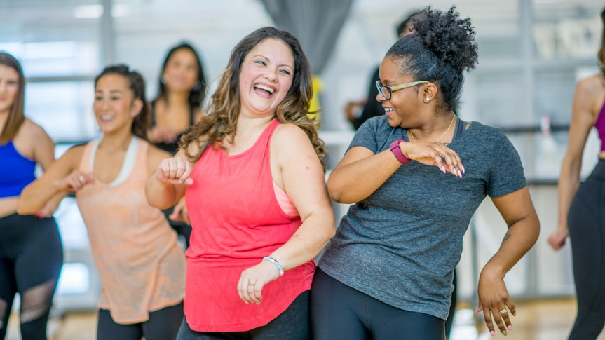 A multi-ethnic group of adult women are dancing in a fitness studio.