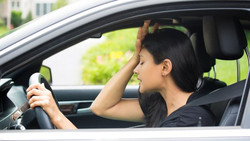 Closeup portrait, angry young sitting woman pissed off by drivers in front of her, hand on head, isolated city street background.