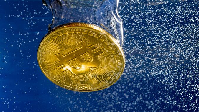 MORGANTOWN, WV - 17 JANUARY 2018: Bitcoin coin sinking through water to illustrate cybercurrencies and falling prices.