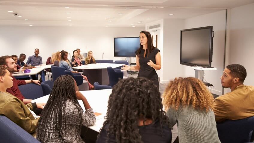 Female teacher addressing university students in a classroom.