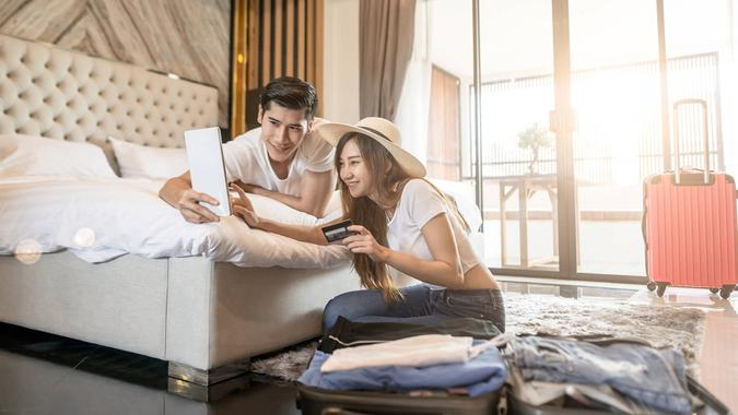 Happy couple packing suitcase on floor in room use tablet for search travel trip online use credit card.