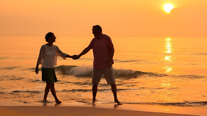 Senior couple walking at beach.