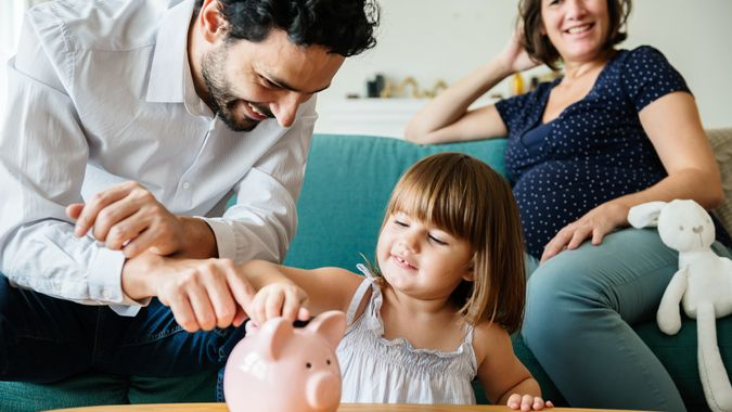 Family saving money in piggy bank.