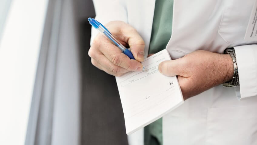 Close up of a doctor filling out a prescription.