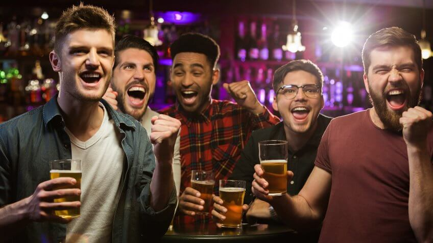 Four happy men holding beer mugs and gesturing while watching TV in bar or pub.
