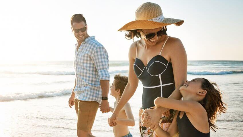 Shot of a family of four spending the day at the beach.