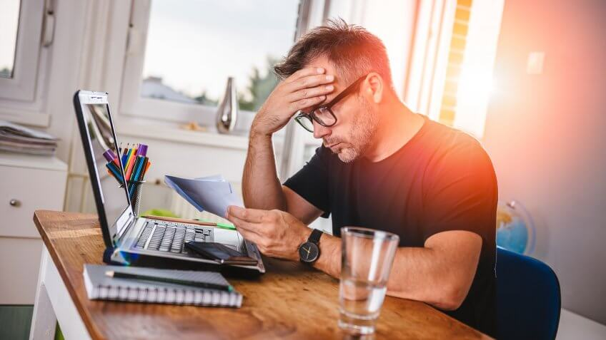 Man sitting in home office, reading letter and felling worried.