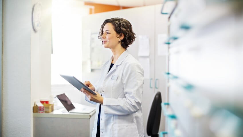 Female pharmacist with a digital tablet standing at chemist store.