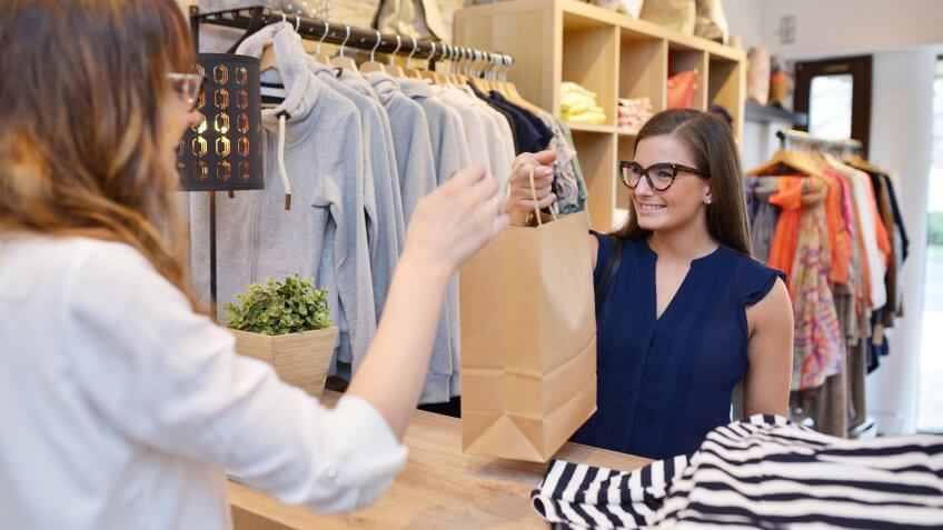 Young woman happily shopping in a women's fashion boutique.