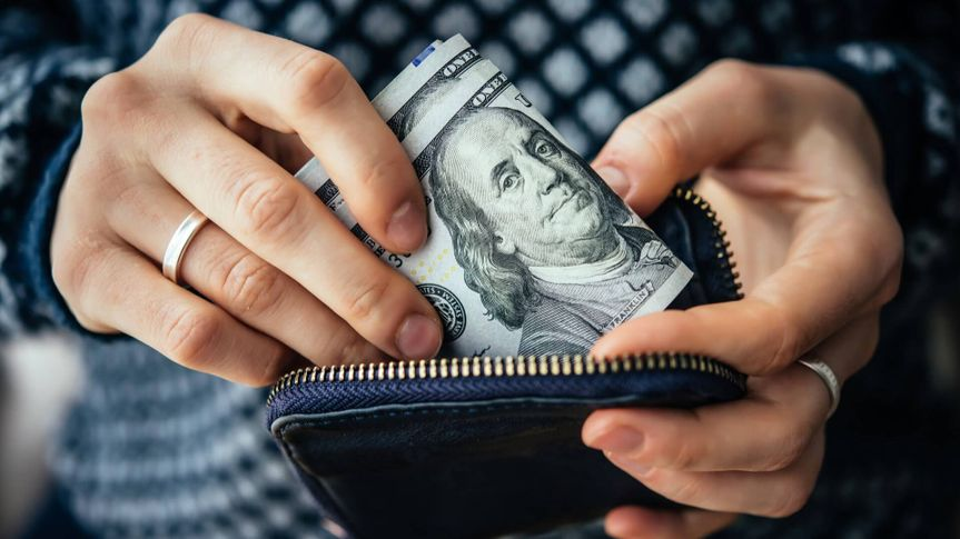 woman putting hundred dollar bills in her purse wallet