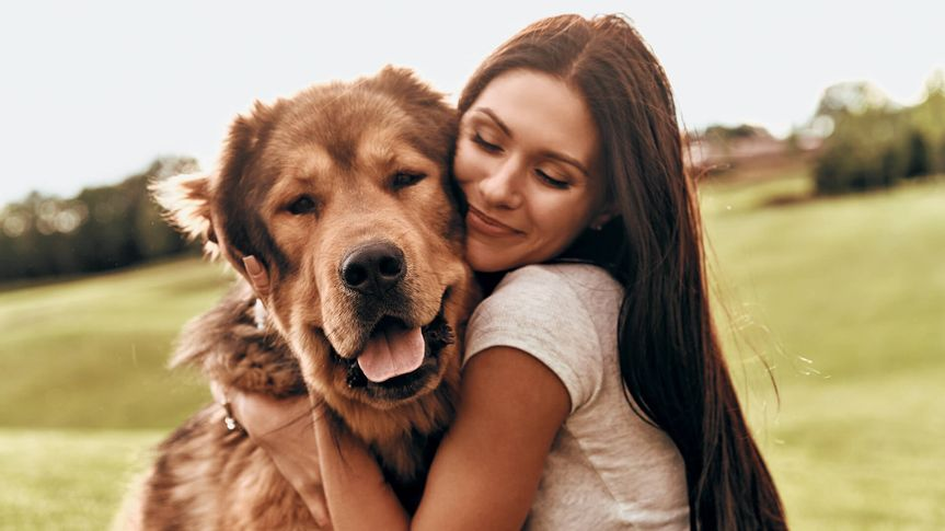 Beautiful young woman keeping eyes closed and smiling while embracing her dog outdoors.
