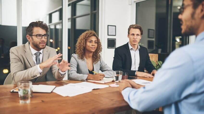Shot of a group of businesspeople interviewing a candidate in an office.