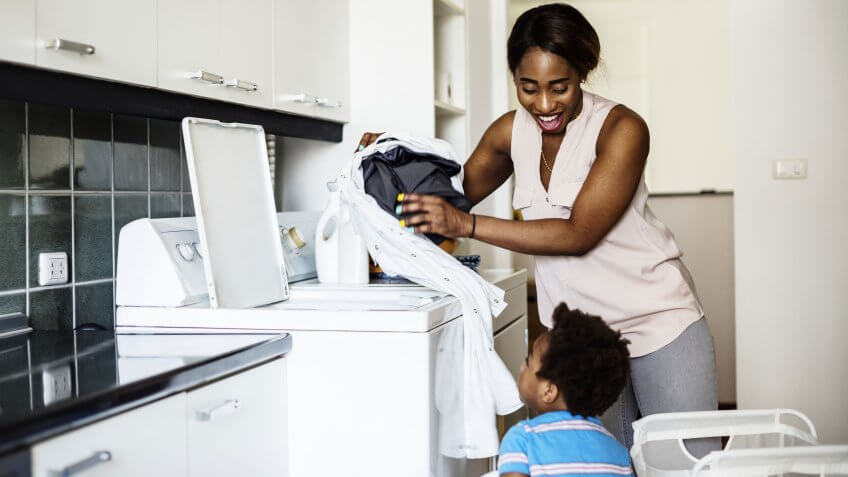 kid helping mom doing the laundry.