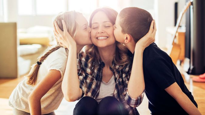Close up photo of son and daughter kissing their mom.