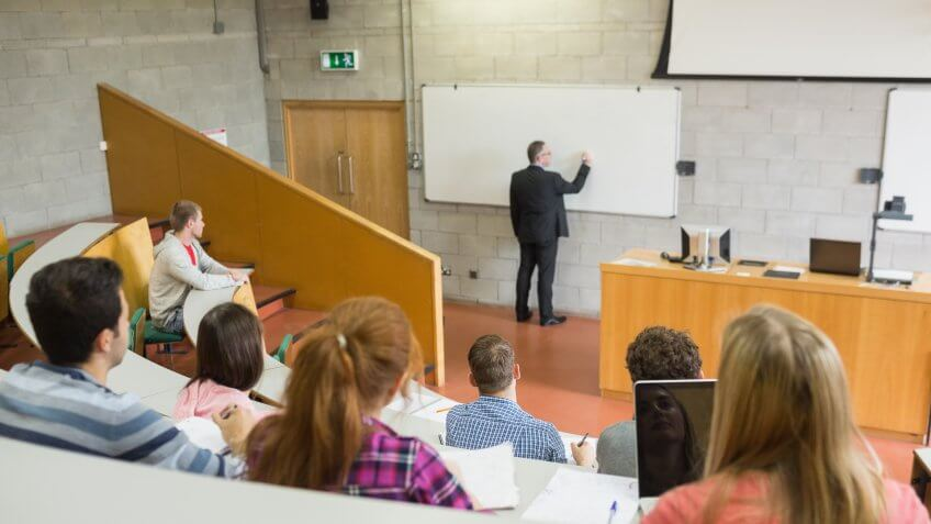 Rear view of a male teacher with students at the college lecture hall.